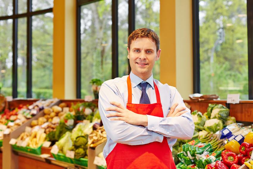 Marktleiter in einem Supermarkt steht vor dem frischen Gemüse